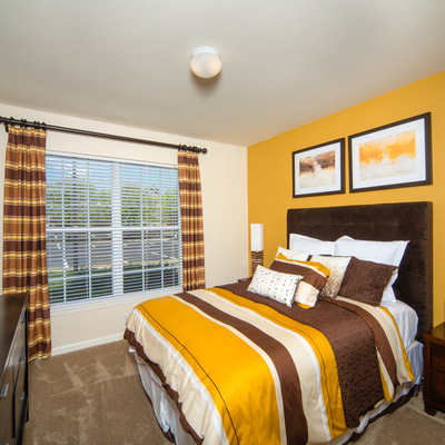 bedroom with carpeting and yellow accent wall